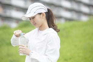 ペットボトルを開封する日本人女性の写真素材 [FYI04636563]
