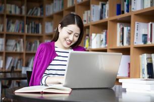 図書室でPCに向かって勉強する日本人女性の写真素材 [FYI04636713]
