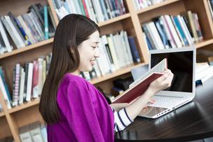 図書室でPCに向かって勉強する日本人女性の写真素材 [FYI04636715]