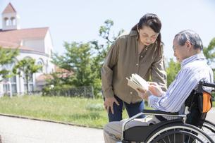 本を読む車椅子に乗った男性と女性の写真素材 [FYI04637066]