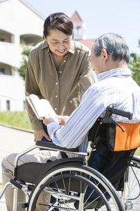 本を読む車椅子に乗った男性と女性の写真素材 [FYI04637067]