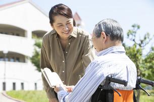 本を読む車椅子に乗った男性と女性の写真素材 [FYI04637068]