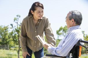 本を読む車椅子に乗った男性と女性の写真素材 [FYI04637069]
