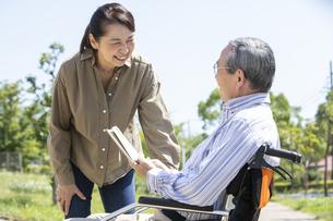 本を読む車椅子に乗った男性と女性の写真素材 [FYI04637071]