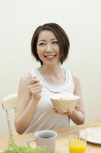 グラノーラを食べる笑顔の女性の写真素材 [FYI04637236]