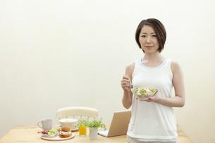 サラダを食べる笑顔の女性の写真素材 [FYI04637241]