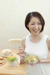 サラダを食べる笑顔の女性の写真素材 [FYI04637243]