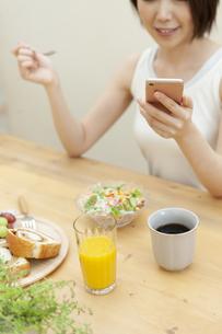 スマートフォンを見ている笑顔の女性の写真素材 [FYI04637245]