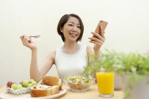 スマートフォンを見ている笑顔の女性の写真素材 [FYI04637247]