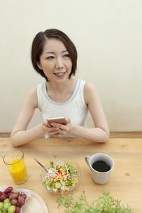 スマートフォンを持っている笑顔の女性の写真素材 [FYI04637251]