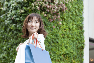 ショッピングバッグを持つ笑顔の女性の写真素材 [FYI04637332]