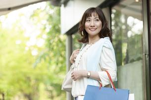 ショッピングバッグを持つ笑顔の女性の写真素材 [FYI04637335]