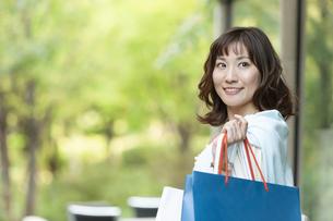 ショッピングバッグを持つ笑顔の女性の写真素材 [FYI04637336]