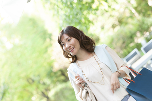 ショッピングバッグを持つ笑顔の女性の写真素材 [FYI04637351]