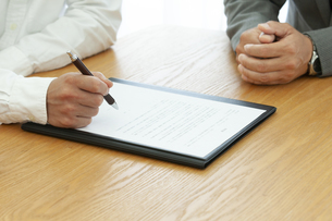 契約書にサインする男性の手元の写真素材 [FYI04637730]