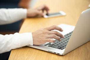 スマートフォンとノートパソコンを操作する男性の手元の写真素材 [FYI04637731]