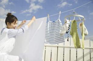 青空の下で洗濯物を干す女性の写真素材 [FYI04638047]