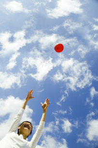 飛んでいく風船をつかもうとする女性の写真素材 [FYI04638053]