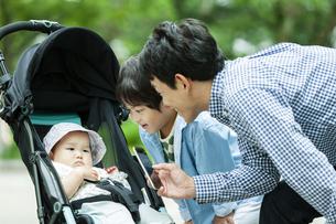 ベビーカーに乗る赤ちゃんの様子を撮影する父親の写真素材 [FYI04638521]
