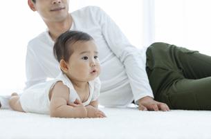 寝転ぶ父親と赤ちゃんの写真素材 [FYI04638614]