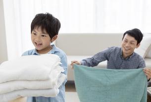 洗濯物を畳む親子の写真素材 [FYI04638621]
