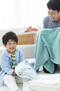 洗濯物を畳む親子の写真素材 [FYI04638626]