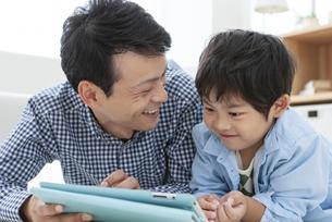 リビングでタブレットPCを見る親子の写真素材 [FYI04638631]