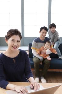 パソコンを操作する母親と家族の写真素材 [FYI04638670]