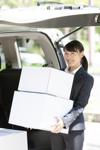 荷物を運ぶビジネスウーマンの写真素材 [FYI04639129]