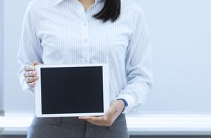 タブレットPCを持つビジネスウーマンの手元の写真素材 [FYI04639341]