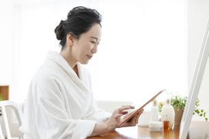 タブレットPCを操作するミドル女性の写真素材 [FYI04639674]