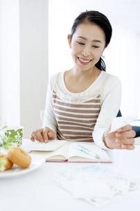 家計簿をつけるミドル女性の写真素材 [FYI04639696]
