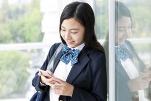スマートフォンを操作する女子学生の写真素材 [FYI04639841]