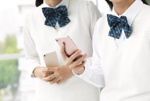 スマートフォンを持つ女子学生の手元の写真素材 [FYI04639874]