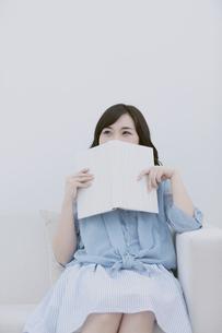 本で顔を隠す女性の写真素材 [FYI04640386]