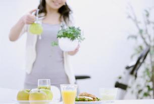 テーブルに並ぶ朝食と女性の写真素材 [FYI04640634]