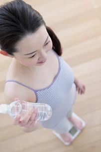 ペットボトルを持ち体重計に乗る女性の写真素材 [FYI04640683]