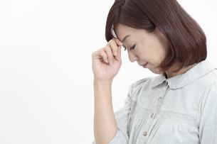 眉間を押さえる中年女性の写真素材 [FYI04640977]