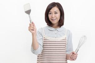 キッチン用品を持つ中年女性の写真素材 [FYI04640985]