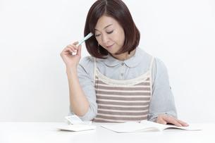家計簿をつける中年女性の写真素材 [FYI04641012]