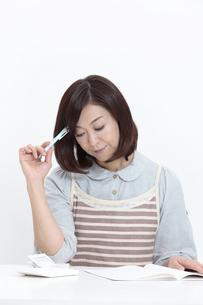 家計簿をつける中年女性の写真素材 [FYI04641013]