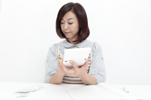 電卓を使う中年女性の写真素材 [FYI04641014]