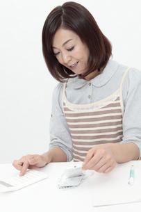 電卓を使う中年女性の写真素材 [FYI04641015]