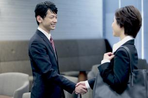 握手するビジネスマンとビジネスウーマンの写真素材 [FYI04641314]