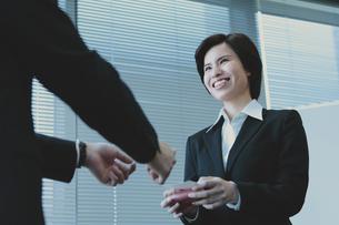 名刺交換するビジネスマンとビジネスウーマンの写真素材 [FYI04641340]