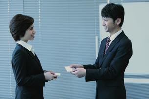 名刺交換するビジネスマンとビジネスウーマンの写真素材 [FYI04641343]