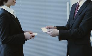 名刺交換するビジネスマンとビジネスウーマンの写真素材 [FYI04641344]