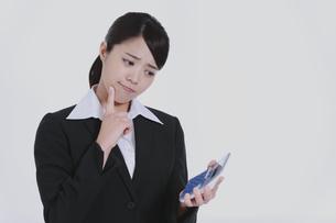 電卓を持って悩むビジネスウーマンの写真素材 [FYI04641717]