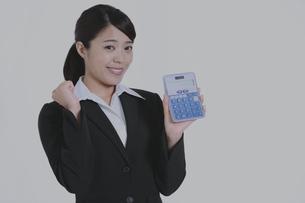 電卓を持ちガッツポーズをするビジネスウーマンの写真素材 [FYI04641720]