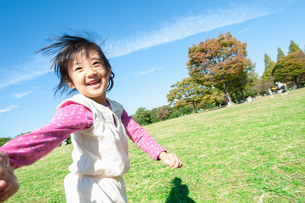 公園で楽しそうに走る女の子の写真素材 [FYI04641835]